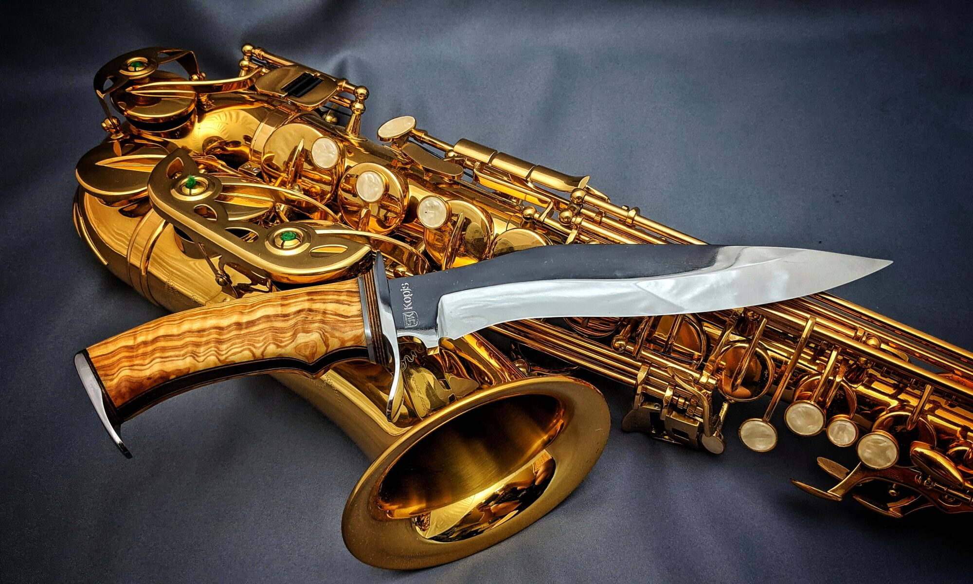 Beauty shot of a Kopis style handmade knife in front of Saxophone full width